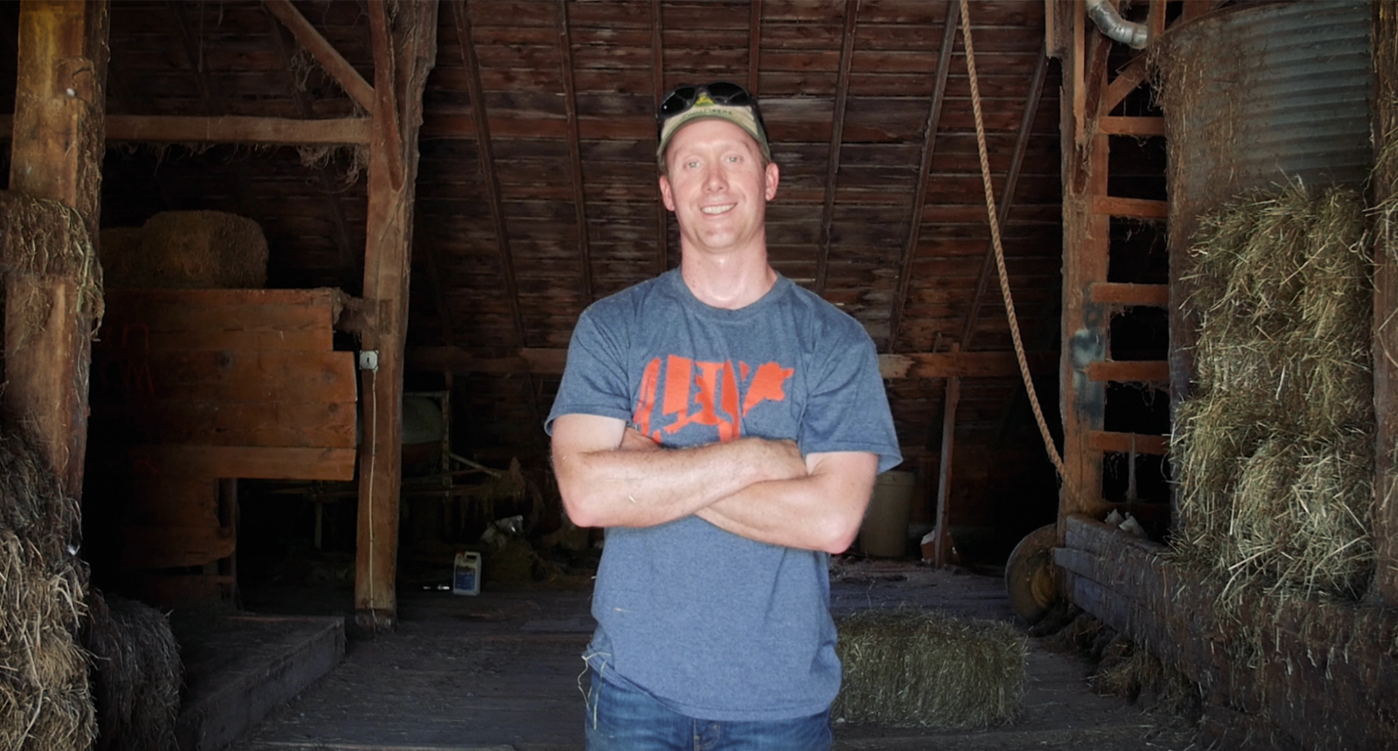 Man standing with arms crossed inside a barn.