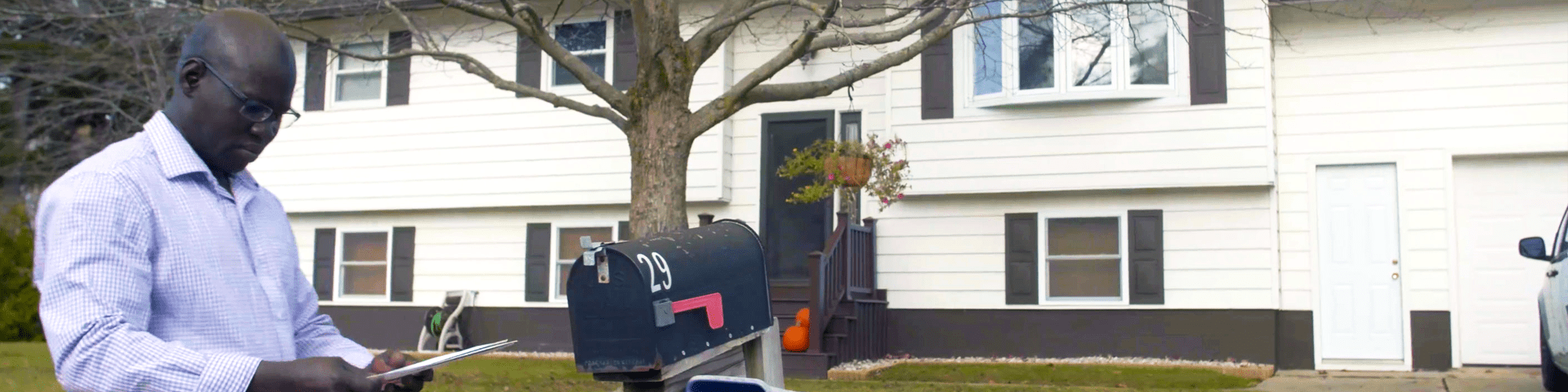 A man in front of his home, checking his mail at the mailbox